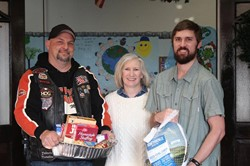 "Portsmouth Motorcycle Club's Tim ""Mater"" Clifford presents a full Christmas dinner to Vern Riffe School Principal Tammy Guthrie and teacher Tom Koch."