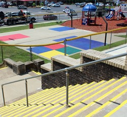 Among other projects, the front steps and the playground basketball court and four-square area were painted on the playground at Vern Riffe School Saturday, July 15, by Serve Day Portsmouth volunteers.