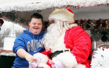 Boy in blue shirt tells Santa his Christmas wish