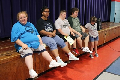 Teens sitting on stage showing off new shoes