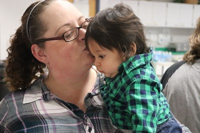 A woman kisses a baby boy on the forehead at a holiday event for families served by Early Intervention