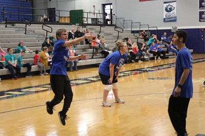 Teen boy in blue Special Olympics shirt jumps as he serves the ball at a volleyball tournament
