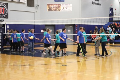 Special Olympics volleyball team shakes hands with opponents under the net after a game