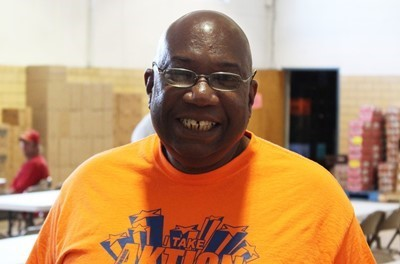 Man in orange shirt smiles at the camera while volunteering in community